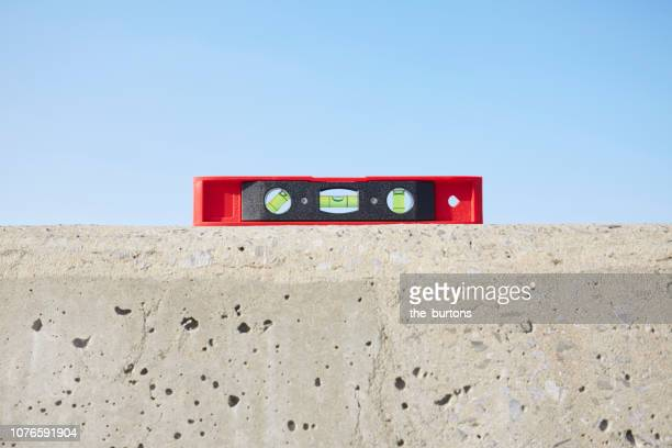 still life of red spirit level on concrete wall against blue sky - wall building feature stock pictures, royalty-free photos & images