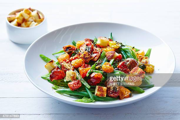 Still life of roast tomato and green bean salad