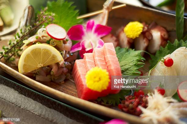 Still life of rustic food with sliced raw fish, fruit and flowers