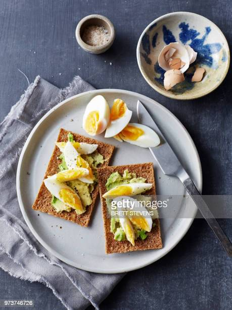 still life of rye crackers with boiled sliced eggs on plate, overhead view - hard boiled eggs stock photos and pictures
