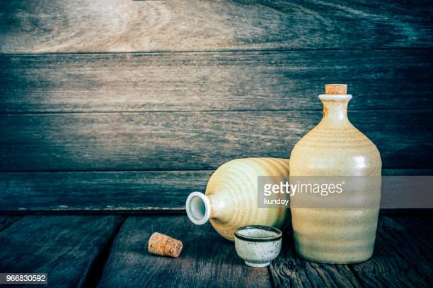 still life of sake bottles with light on wood background. - saki stock photos and pictures