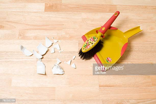 still life of shards broom and dustpan on floor