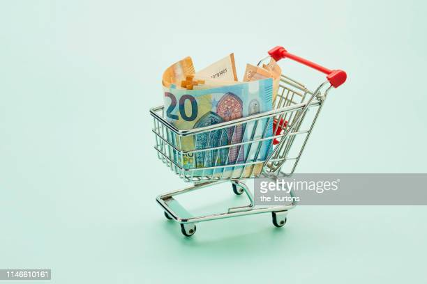 still life of shopping cart and euro notes on turquoise background - ��couter photos et images de collection