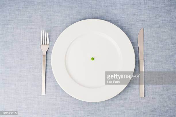 still life of single pill on plate - anorexia stock photos and pictures