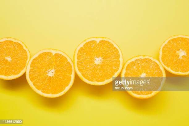 still life of sliced oranges on yellow background - vitamin c stock pictures, royalty-free photos & images