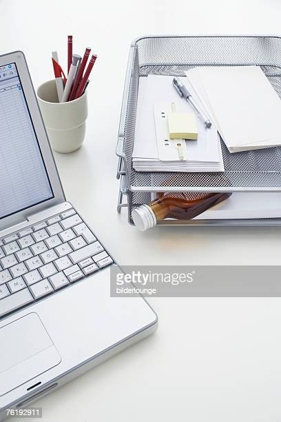 still life of small alcohol bottle in tray on office desk
