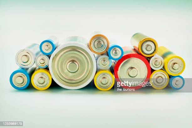 still life of stack of colorful old batteries - alkaline stock pictures, royalty-free photos & images