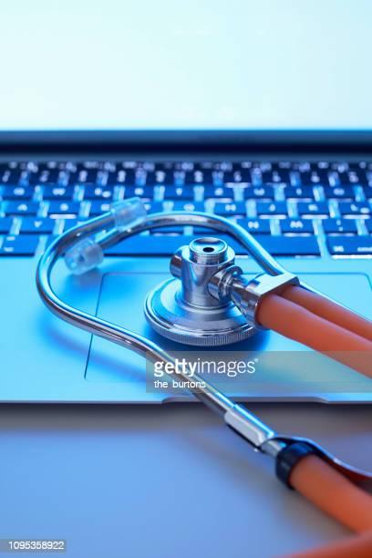 Still life of stethoscope on laptop
