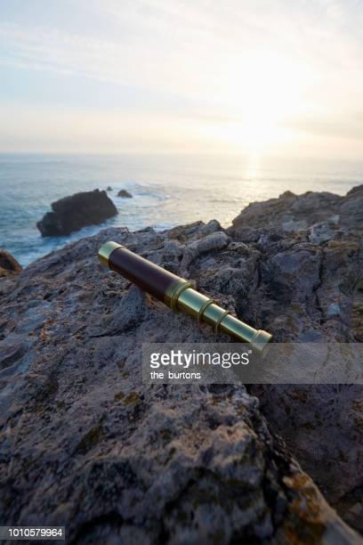 Still life of telescope on rocks by the sea