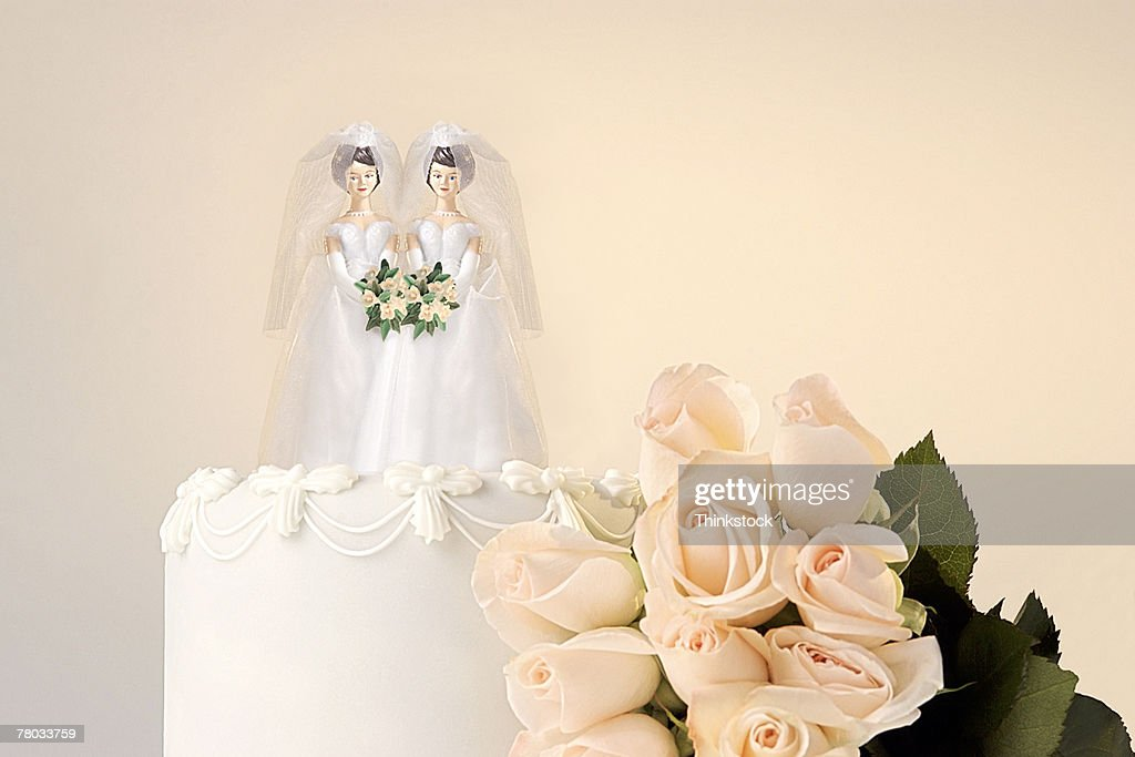 Still life of the top of a wedding cake with two miniature brides cake topper and roses at the side : Stock Photo