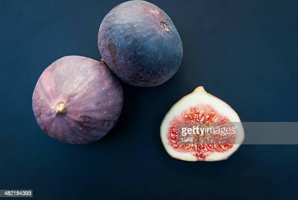 Still life of three figs, one sliced in half