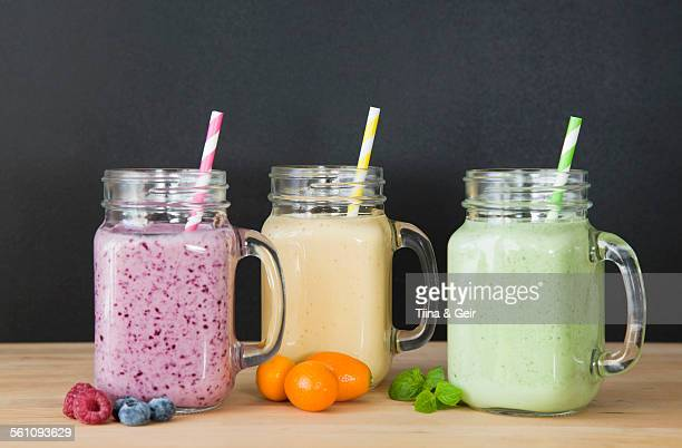Still life of three fresh smoothies and fruit
