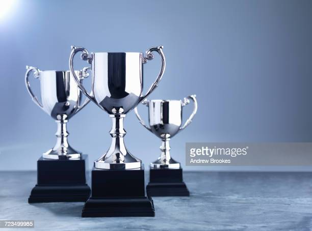 still life of three trophies awaiting the winners presentation - award stock pictures, royalty-free photos & images