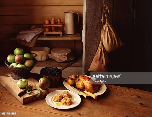 still life of traditional country farm house scene, with cooking apples, roasted guinea fowl and baked apple turnovers - guinea fowl stock pictures, royalty-free photos & images