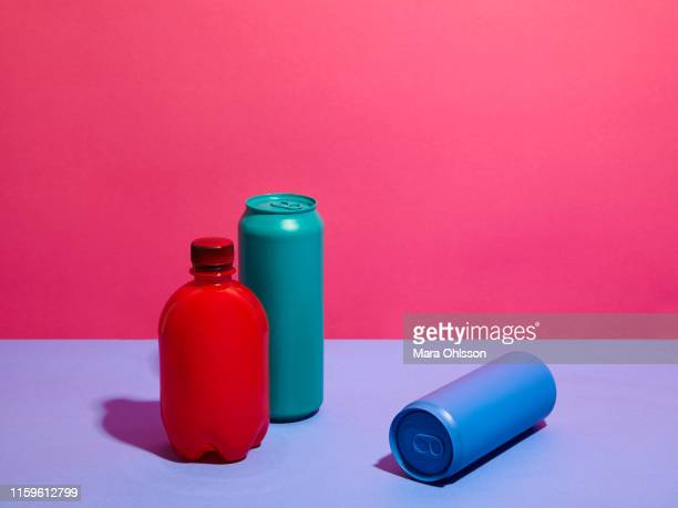 still life of turquoise and blue drink cans with red bottle and pink background - refresco fotografías e imágenes de stock