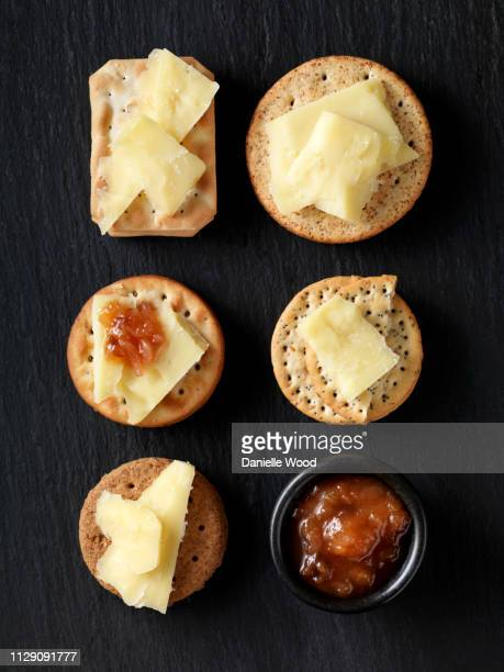 still life of variety of cheese crackers with cheddar cheese and chutney on black slate, overhead view - クラッカー ストックフォトと画像
