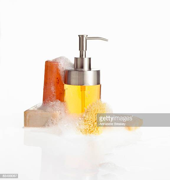 Still life of various soaps with suds and sponge