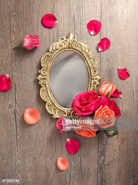 Still life old fashion mirror with roses on wooden background.