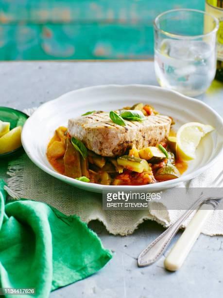 still life plate of tuna, bean and tomato stew with lemon garnish - atún pescado fotografías e imágenes de stock