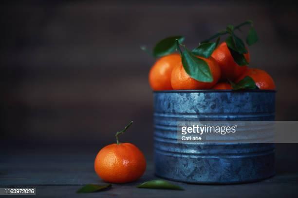stilleven rustiek beeld van mandarijnen in metalen emmer - softfocus stockfoto's en -beelden