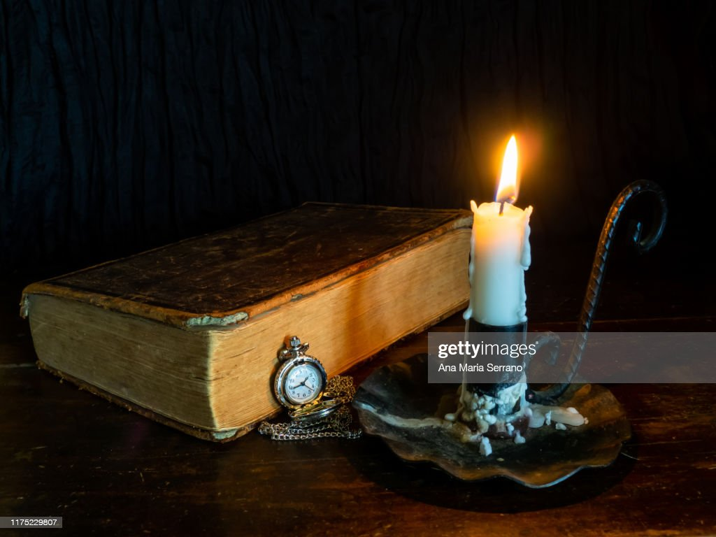 A still life with an ancient bible, a candlestick with a lit candle and a pocket chain watch that symbolize the passage of time : Stock Photo