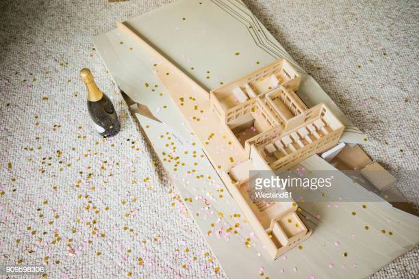 Still life with architectural model, confetti and bottle of champagne