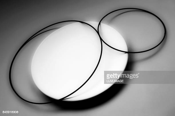 Still life with black circles and a white plate.