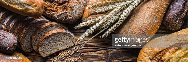 still life with breads and wheats, close-up panoramic image - gluten free bread stock pictures, royalty-free photos & images