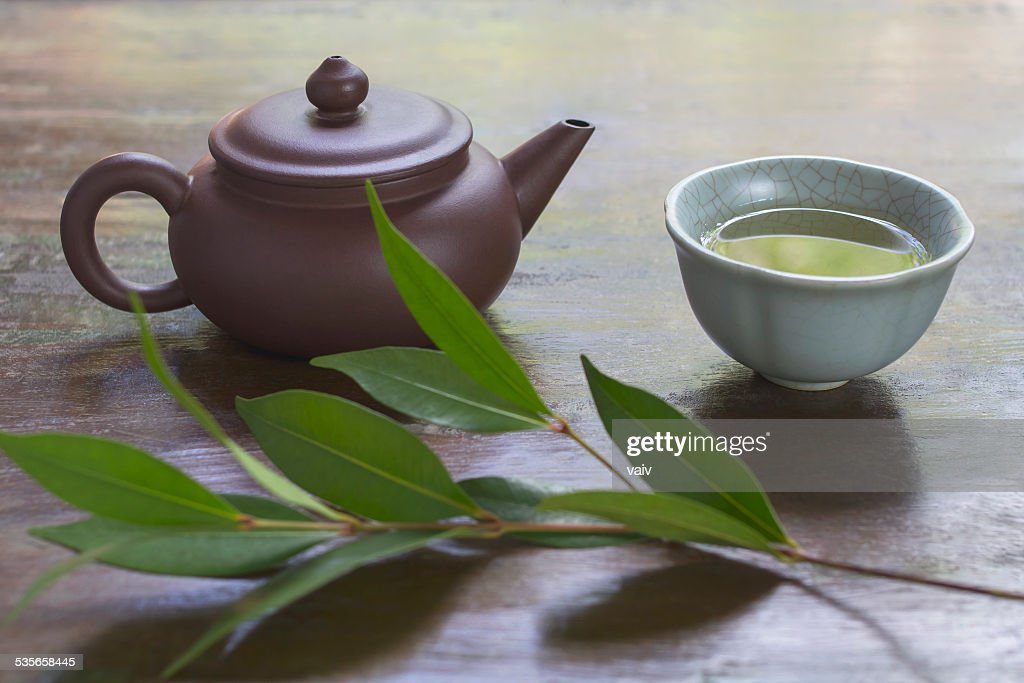 Still life with ceramic teapot, cup of green tea, and branch of tea plant : Stock Photo