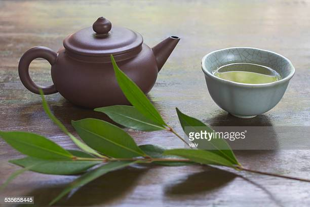 Still life with ceramic teapot, cup of green tea, and branch of tea plant