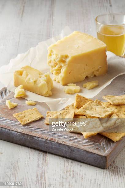 still life with cheddar cheese and crackers on cutting board - cheddar cheese stock pictures, royalty-free photos & images