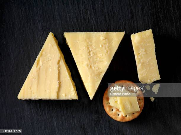 still life with cheese cracker and cheddar cheese triangles on black slate, overhead view - cheddar cheese stock pictures, royalty-free photos & images