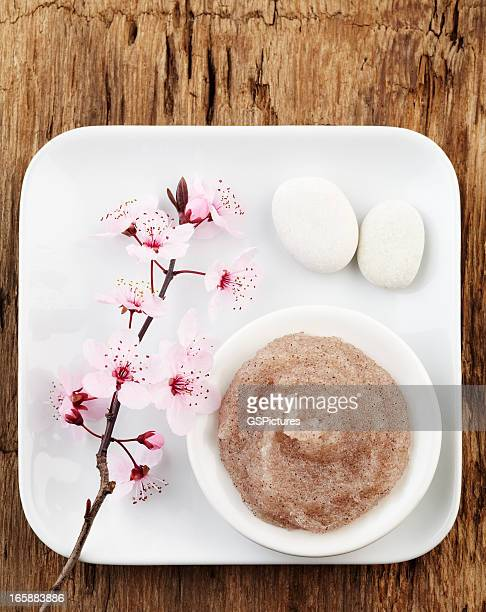 Still life with cherry blossom, salt scrub and white pebbles