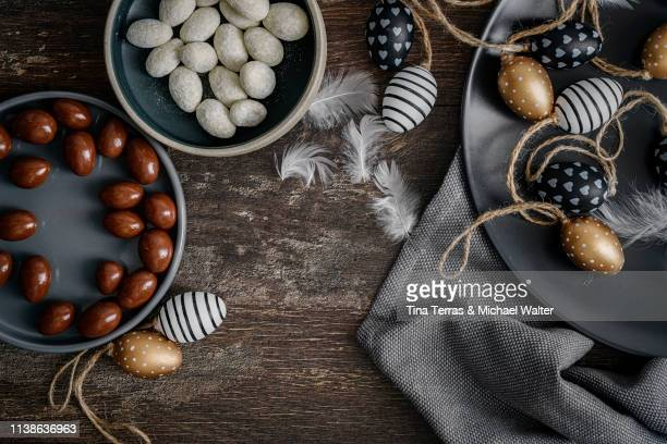 still life with chocolate eggs and easter decoration on a table. - イースターエッグのチョコレート ストックフォトと画像