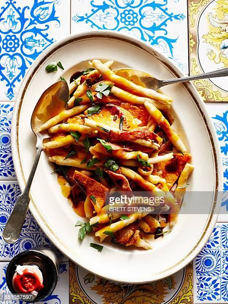 Still life with dish of Italian pumpkin and bacon strozzapetti