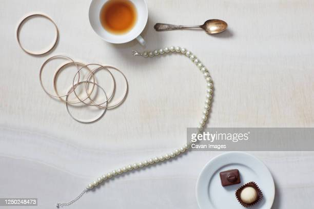 still life with necklace, bracelet, tea, chocolates - necklace stock pictures, royalty-free photos & images