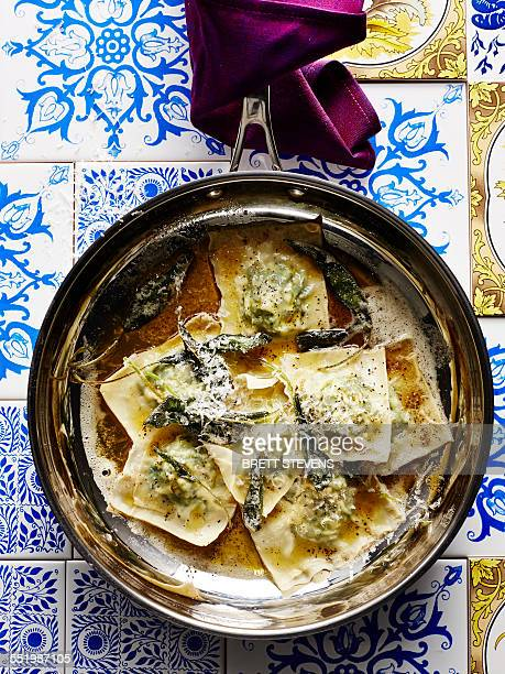 Still life with pan of Italian stinging nettle tortellini and parmesan