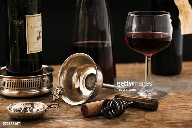 Still life with red wine glass, carafe and bottle on wooden table, studio shot
