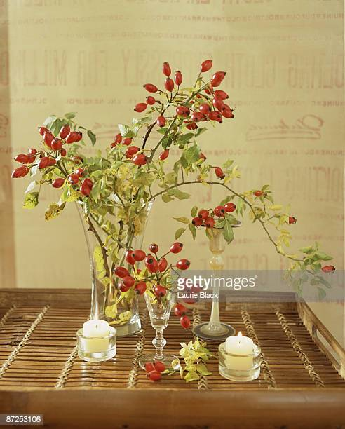 Still life with rosehips and votive candles