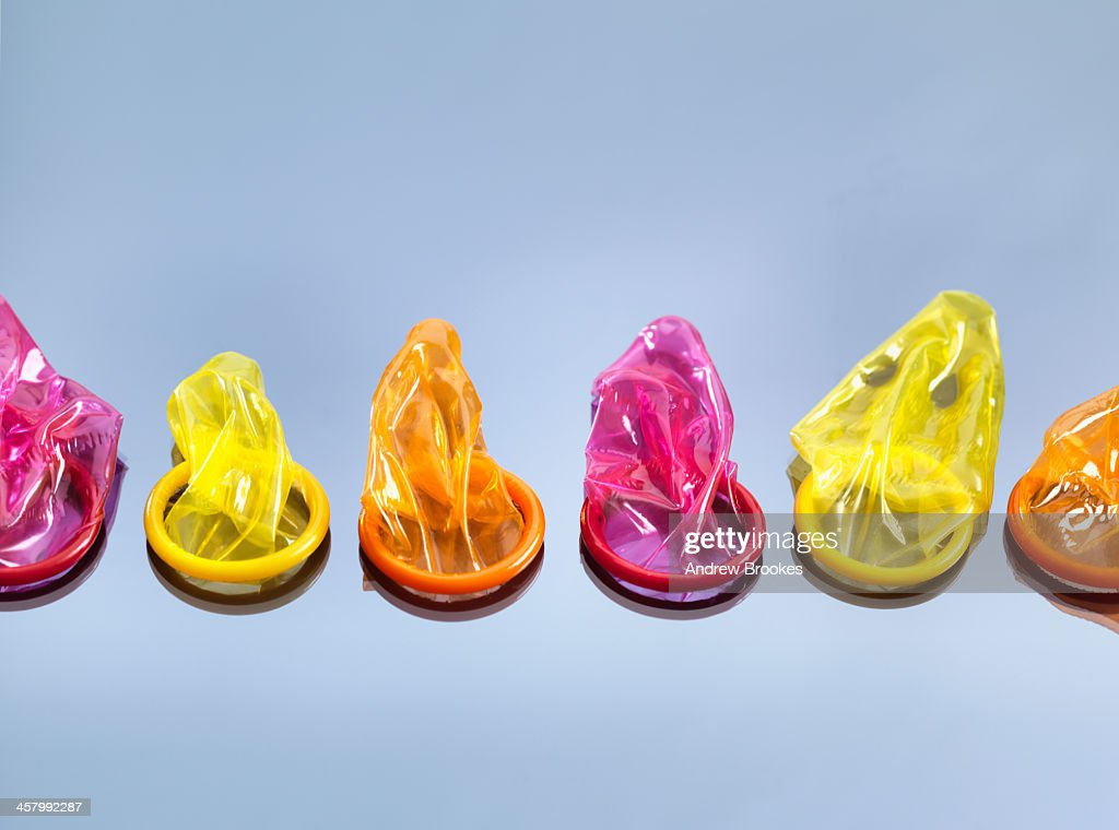 Still life with six colorful condoms, illustrating the decision to take precautions during sex : Stock Photo