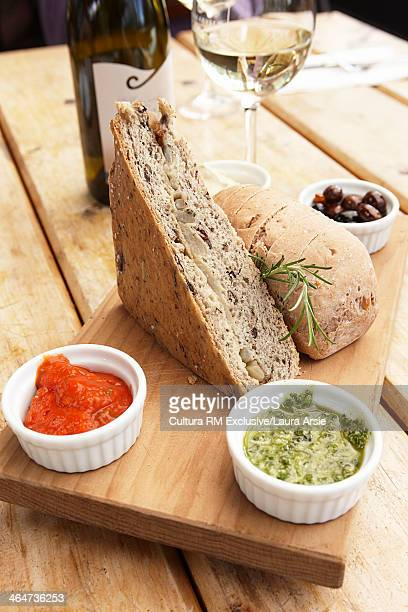 Still life with snack of bread, dipping sauces and white wine