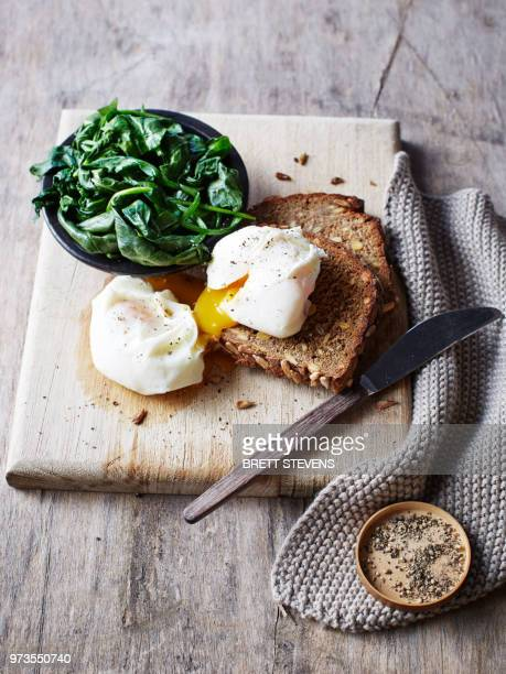 Still life with spinach and poached egg on toast on chopping board, overhead view