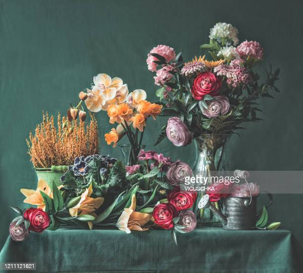 still life with various flowers in pots and vases on table with watering can - flower arrangement stock pictures, royalty-free photos & images