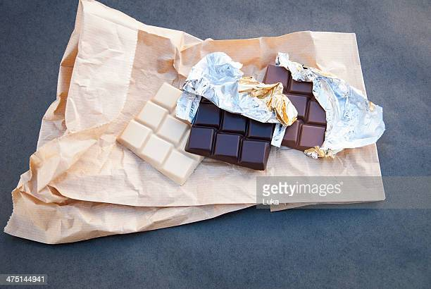 still life with white, dark and milk chocolate - candy wrapper stock photos and pictures