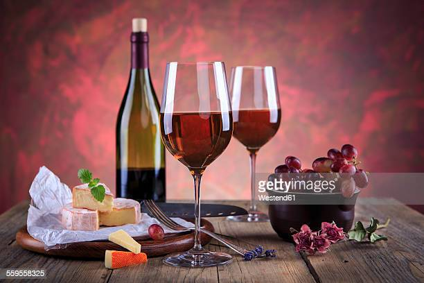 Still life with wine bottle, wine glasses, cheese and grapes
