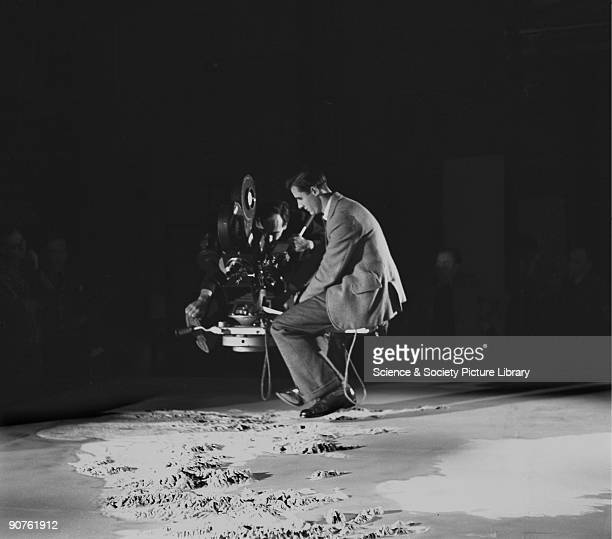 Still photograph taken during the making of the British Transport Films production �Speedup� showing a cameraman and his assistant filming a map of...
