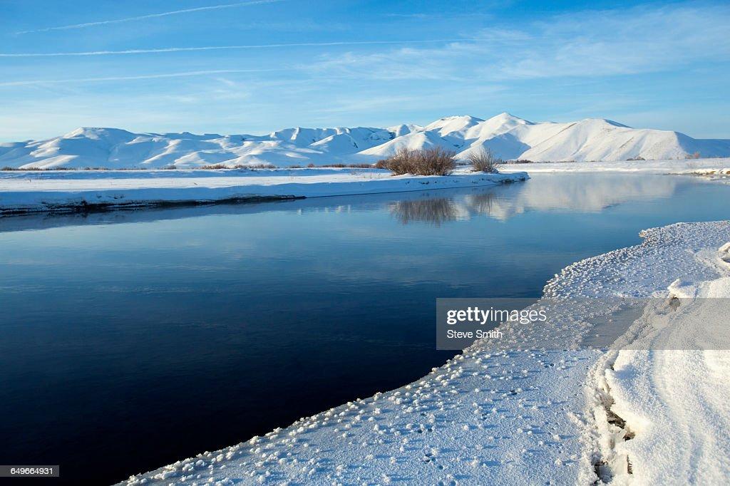 Still river in snowy remote landscape : Stock Photo