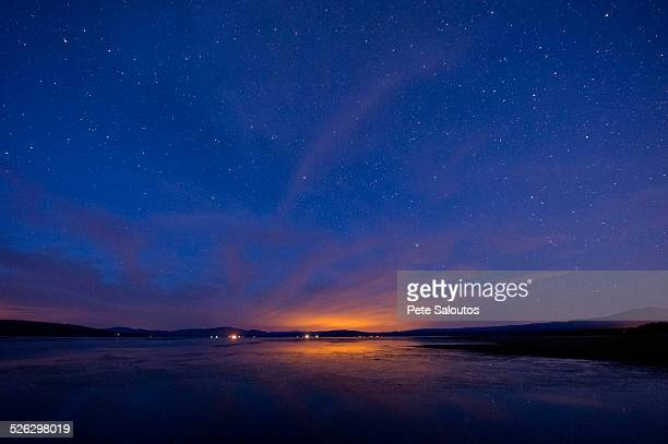 Still rural lake under starry night sky