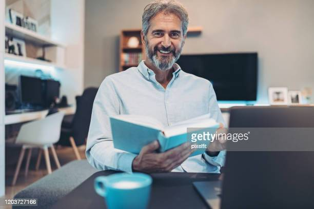still the best way to relax is with a book and a cup of coffee - authors stock pictures, royalty-free photos & images