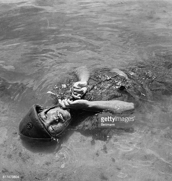 Still wearing his helmet, the body of a Jap soldier floats in the water at Tanapag Harbor, Saipan, after participating in a futile counter-attack...